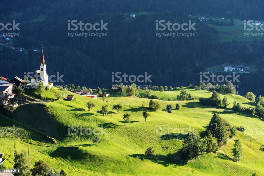 Chapel and sheep on the meadow. Bell tower, trees, shrubs and hilly green grassland. Heiliger Antoniuse church and houses in the evening light. Pitburger See, Taxegg, Salzburg, Austria, Europe stock photo