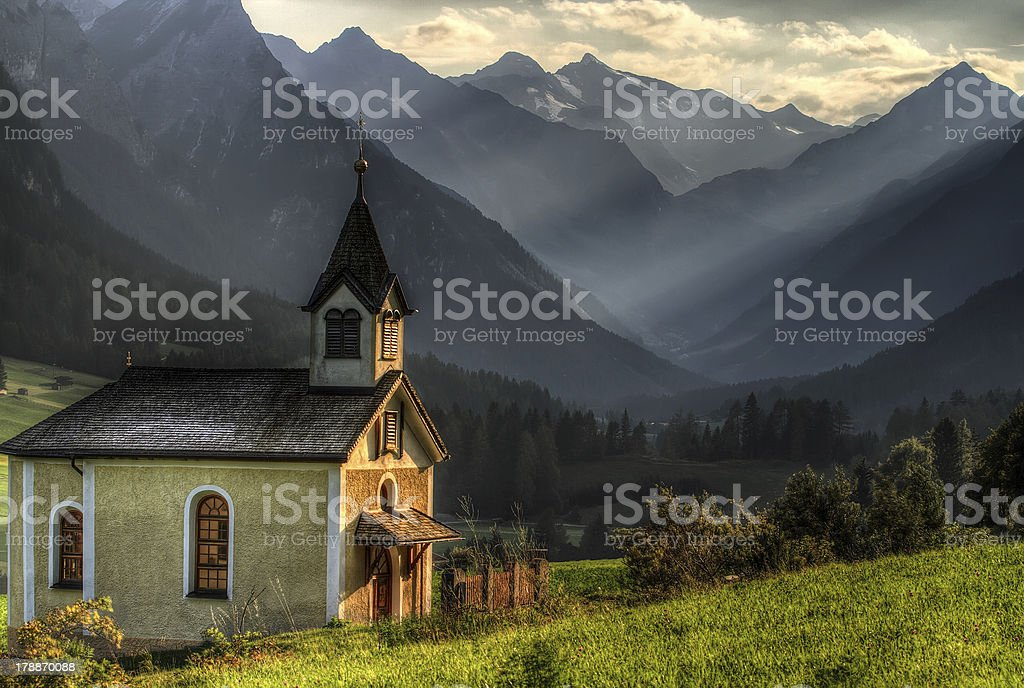 Chapel catching last rays of sun in mountain valley. stock photo