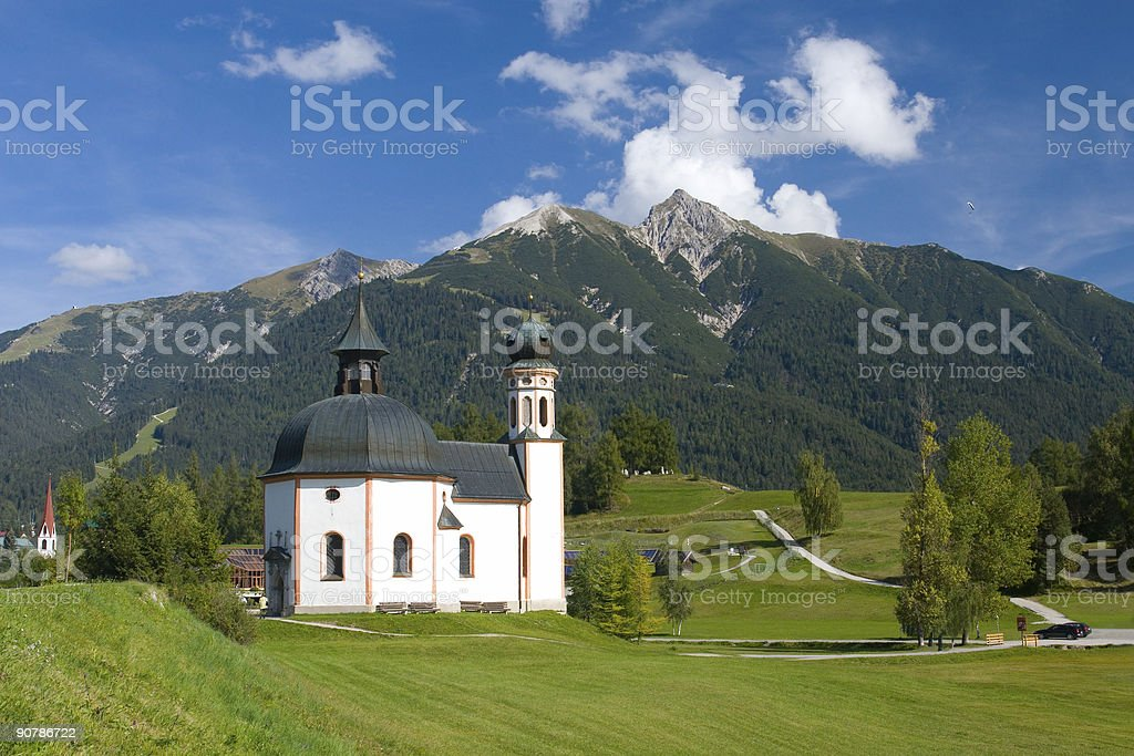 A chapel that stands alone on a mountain stock photo