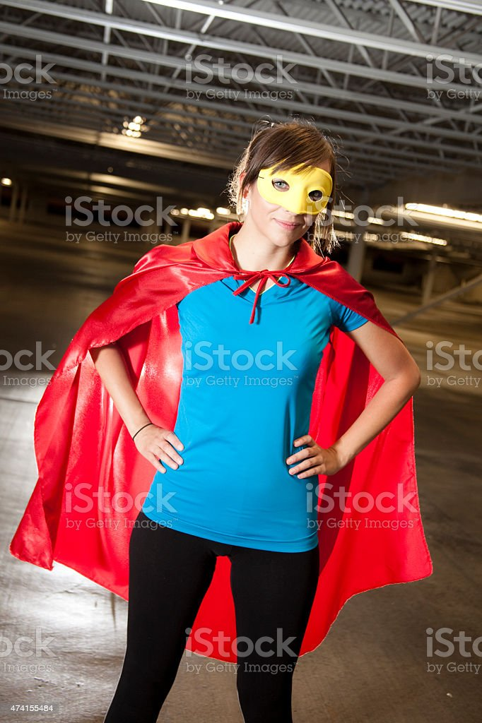 Character: Young adult woman in hero costume. Red cape, mask. stock photo