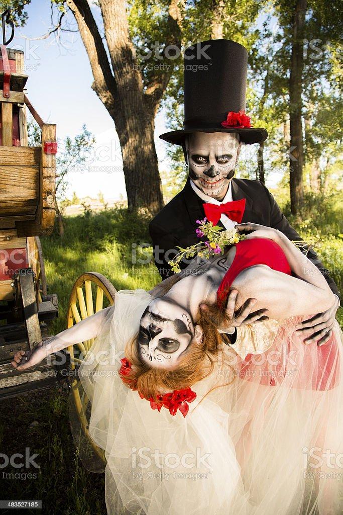 Characters: Skeleton bride wraps arms around groom. Spooky Halloween wedding. stock photo
