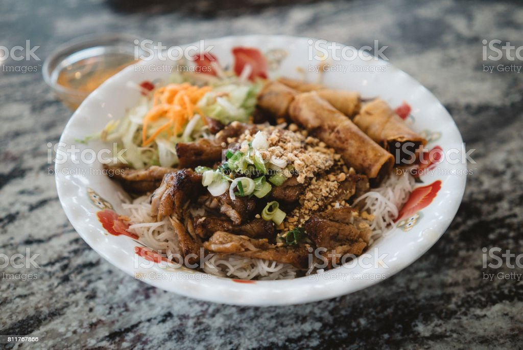 Charbroiled pork and spring rolls on rice vermicelli stock photo