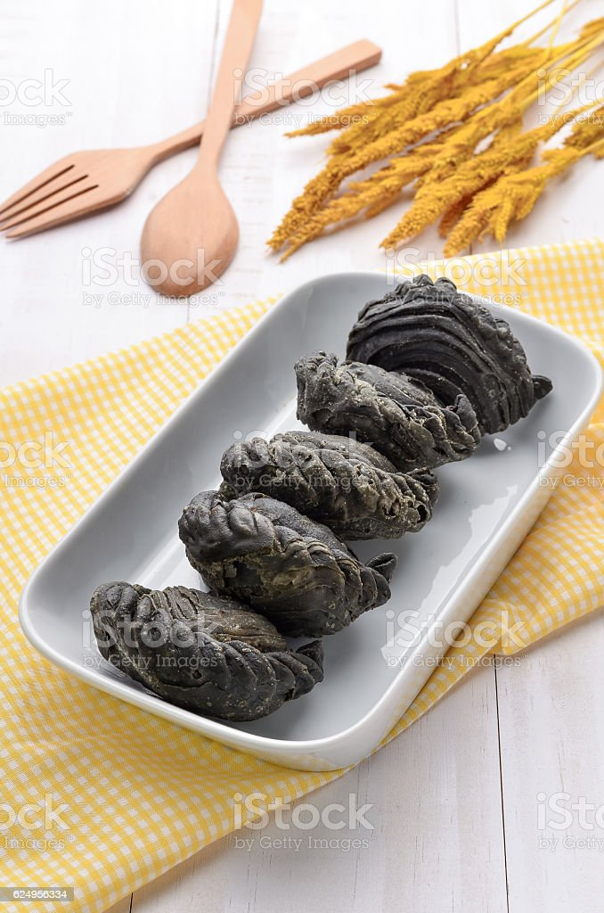 Charcoal curry puff pastry with yellow fabric on white table stock photo