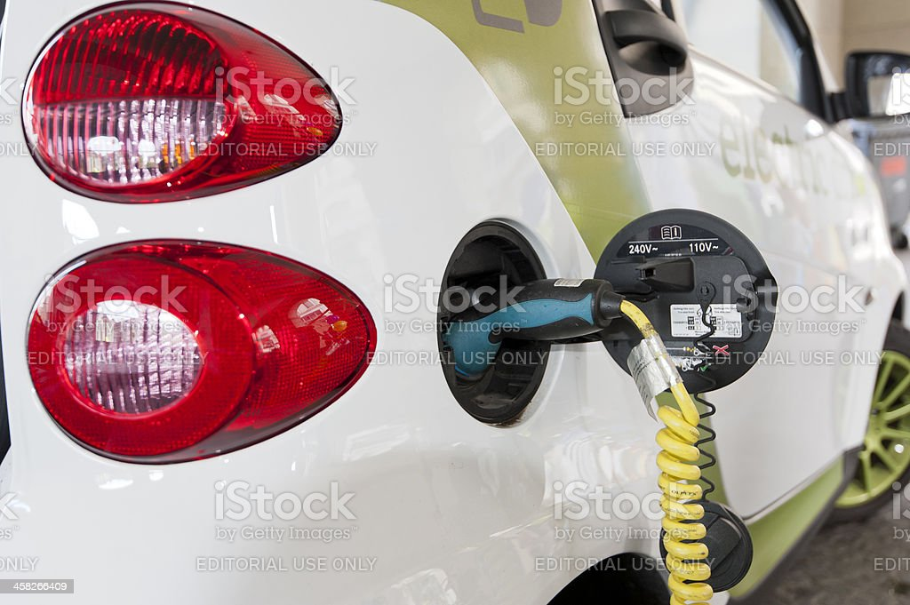 an electrically powered smart car being charged at a fair for...