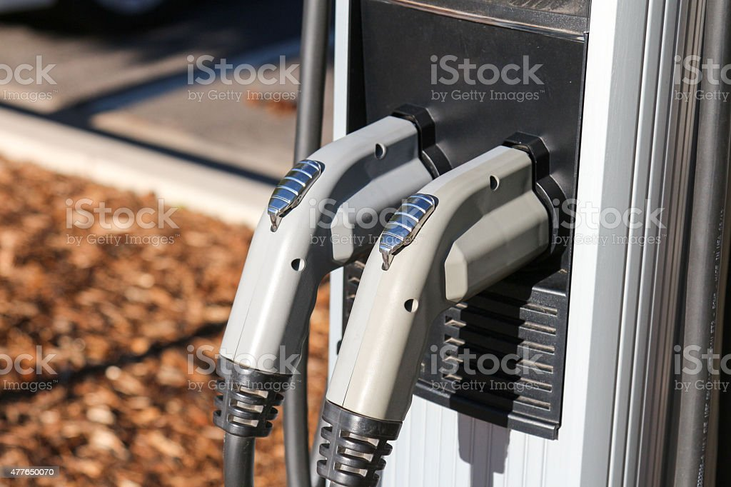 Chargers on an electric vehicle charging station and mulch stock photo