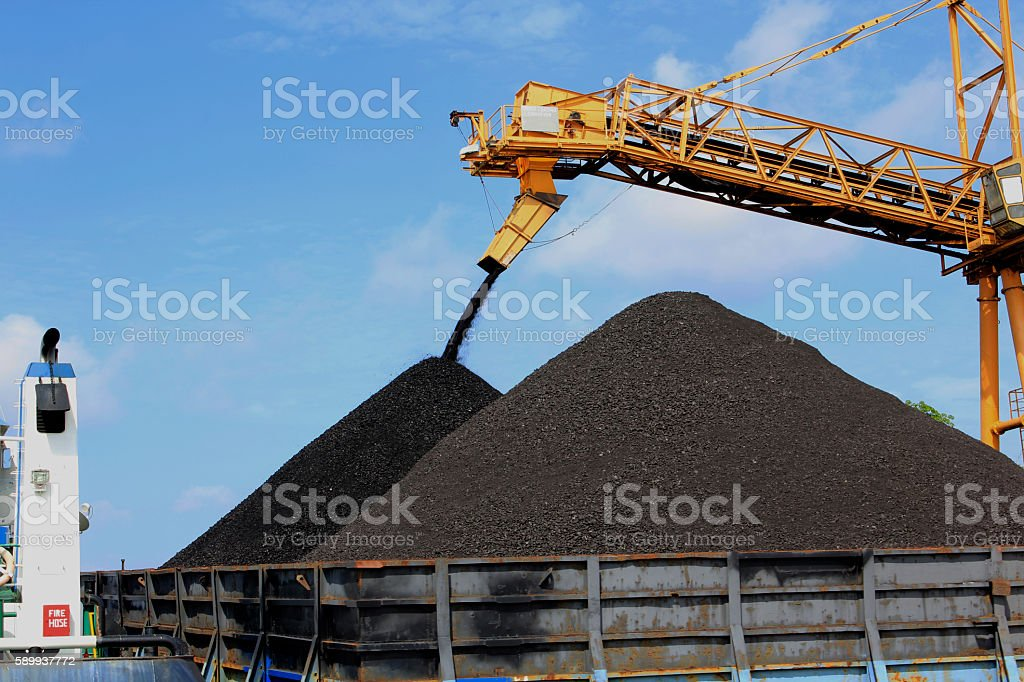 Charging a second mountain of coal stock photo
