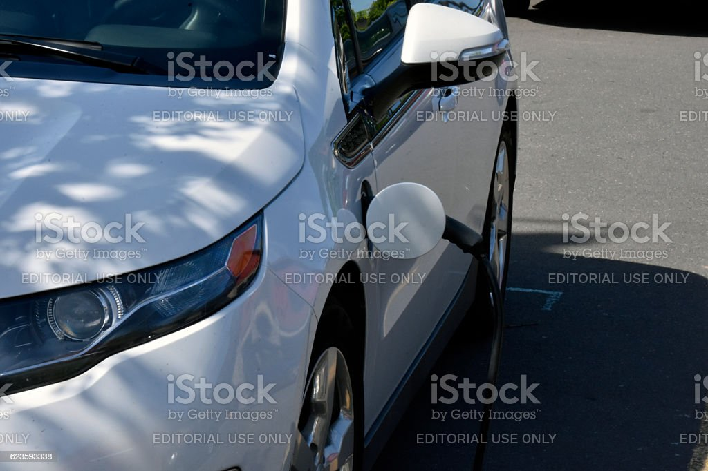 Charging Electric Car in Parking Lot. stock photo