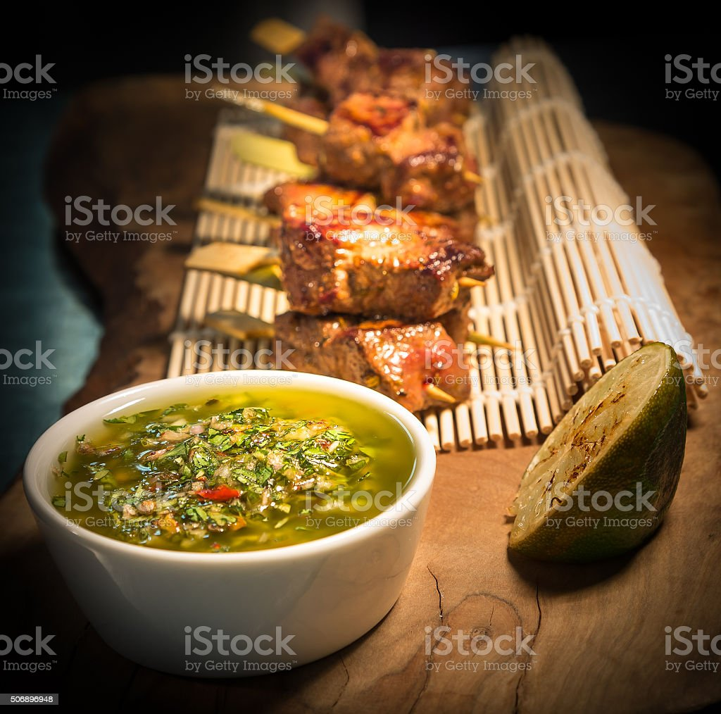 Chargrilled skewered beef with chimichurri green sauce stock photo