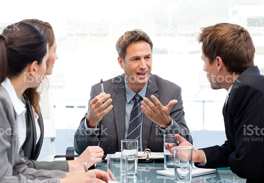 Charismatic chairman talking with his team royalty-free stock photo