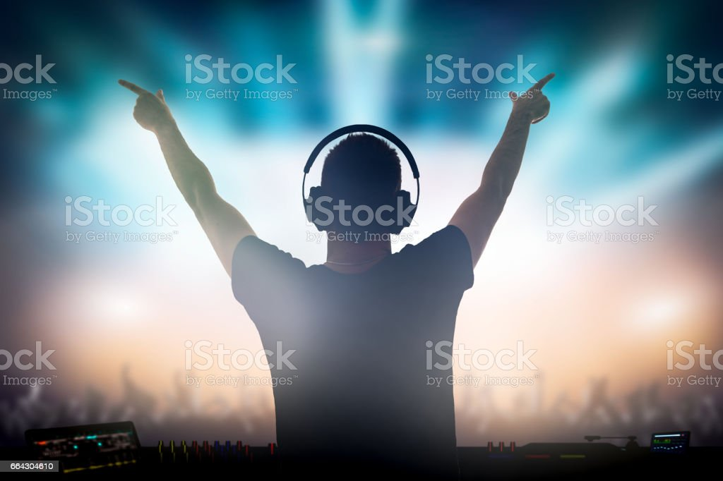 Charismatic disc jockey at the turntable. stock photo