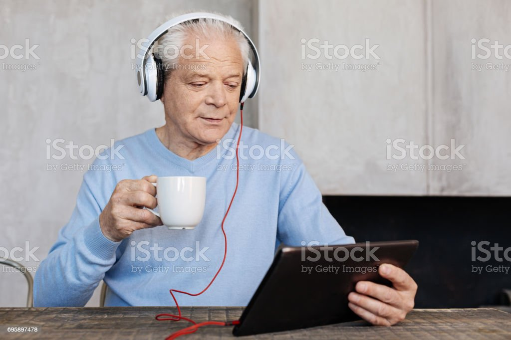 Charismatic handsome gentleman enjoying movies in the morning stock photo