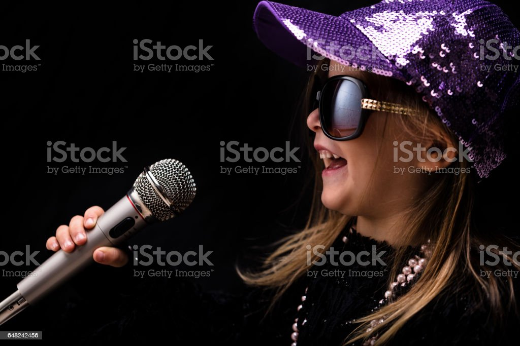 Charismatic trendy little girl singing into a mike stock photo