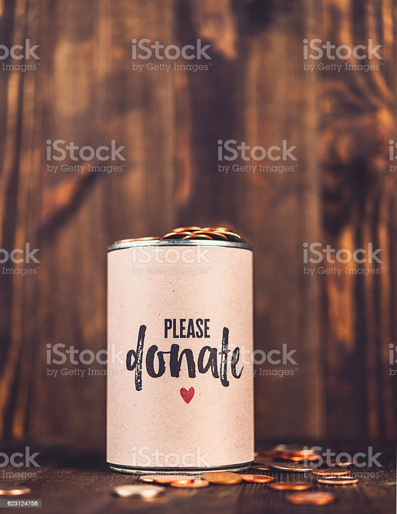 Charity collecting tin against wooden background. American holiday fundraising stock photo