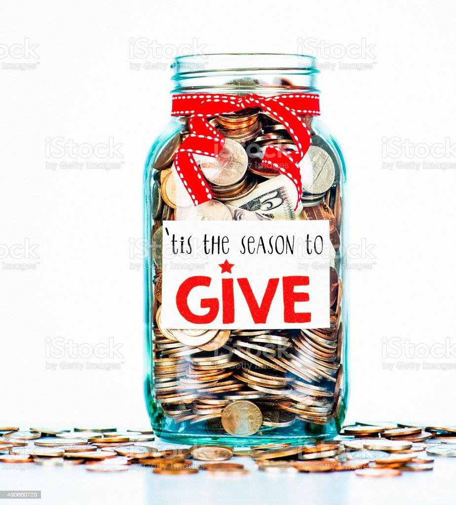 Charity money savings jar with festive message. Holiday fundraising. stock photo