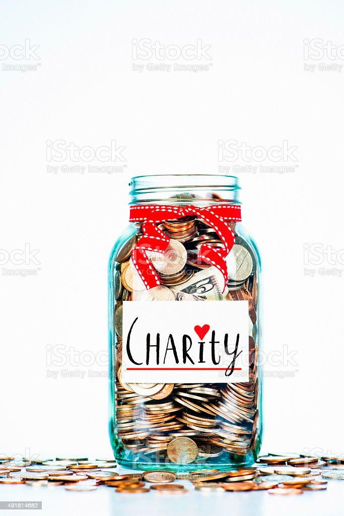 Charity money savings jar with red ribbon. Holiday fundraising. stock photo