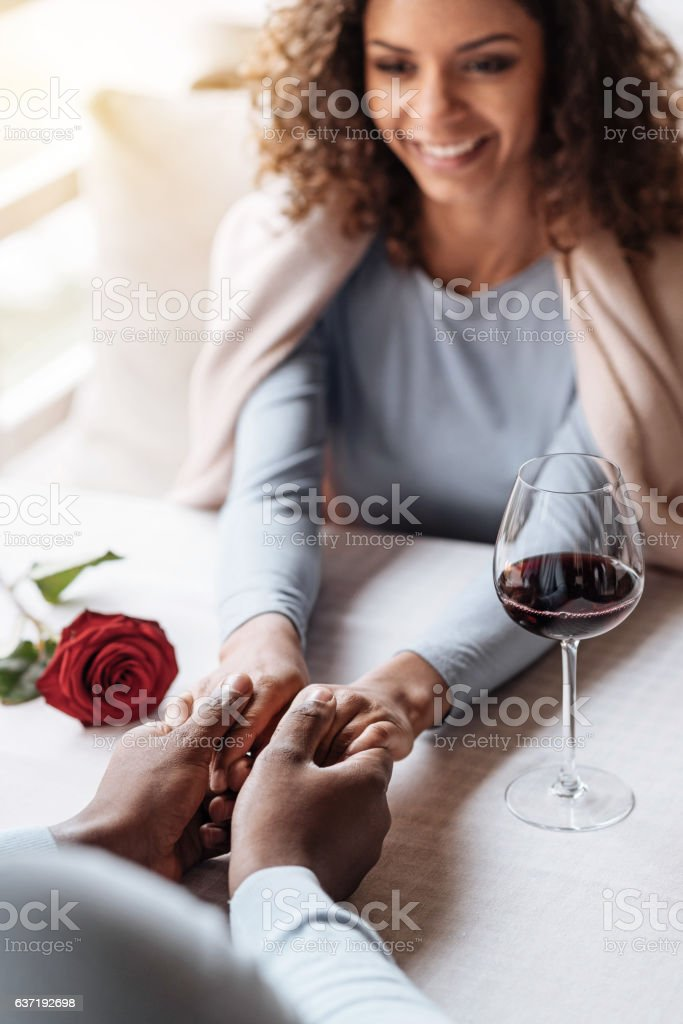 Charming African American woman holding hands with her boyfriend stock photo