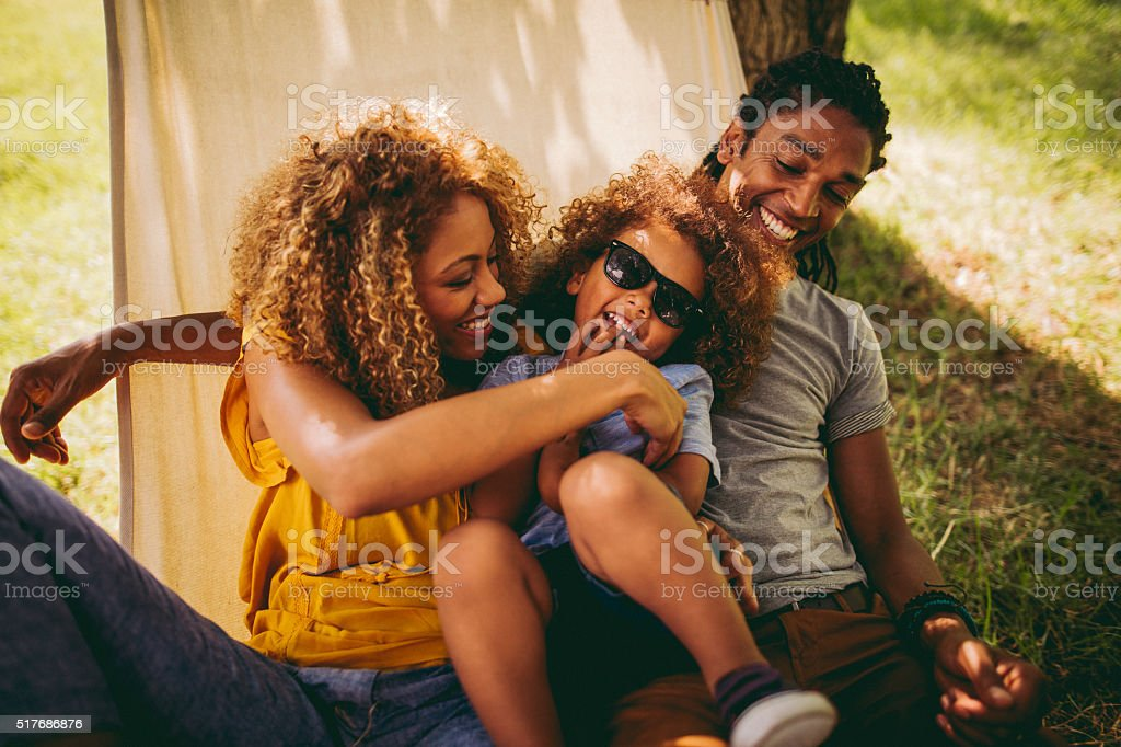 Charming African-American mother and father tickles their adorab stock photo