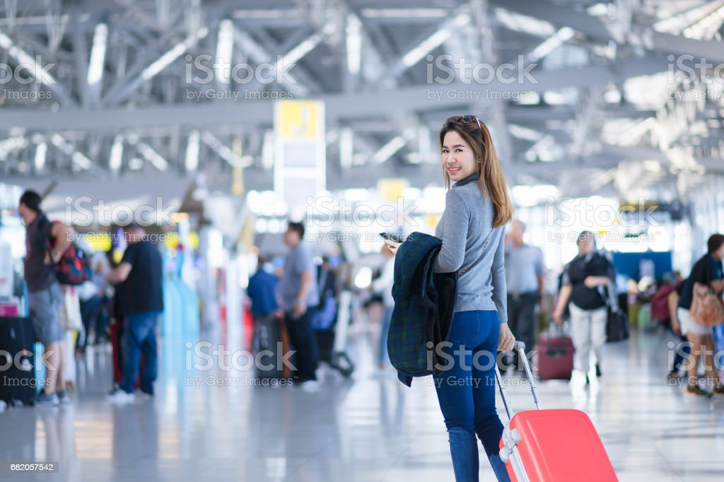 Charming beautiful business woman smile in casual style using smartphone and hold luggage bag for travel with blur the airport terminal. stock photo