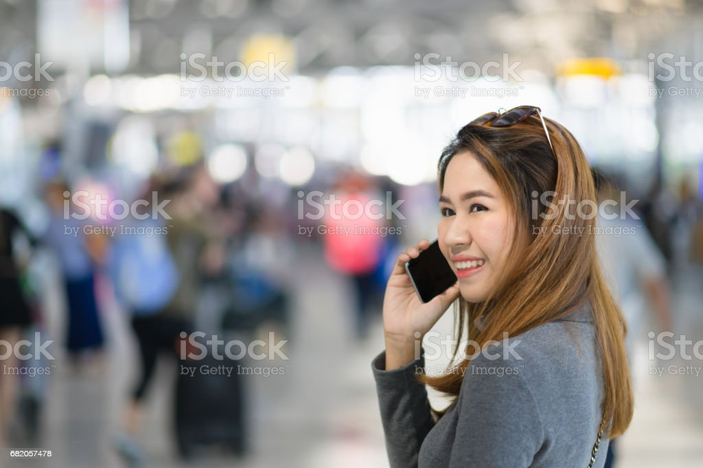 Charming beautiful business woman smile in casual style using smartphone with blur the airport terminal. stock photo