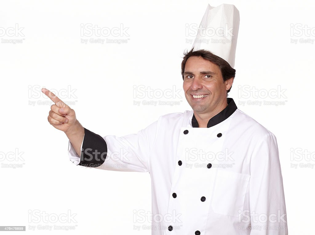 Charming chef pointing to his right royalty-free stock photo