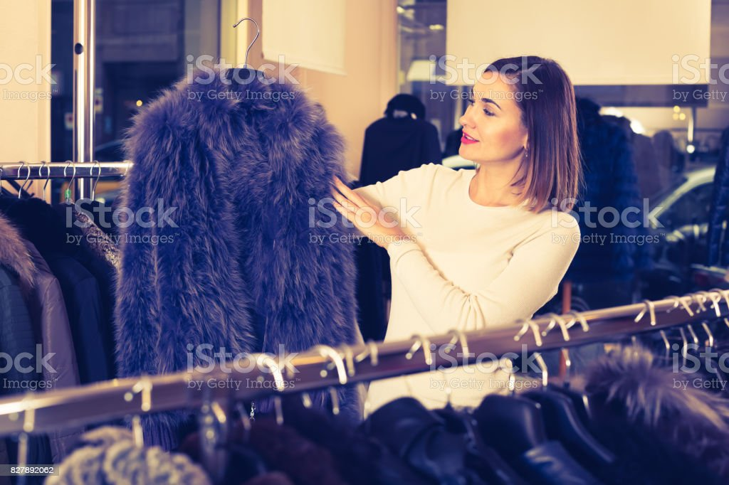 Charming female customer examining blue fur coats stock photo