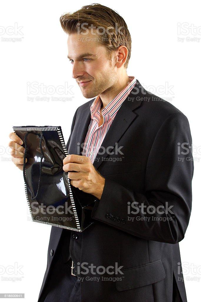 Charming Generous Boyfriend Holding a Gift Bag stock photo