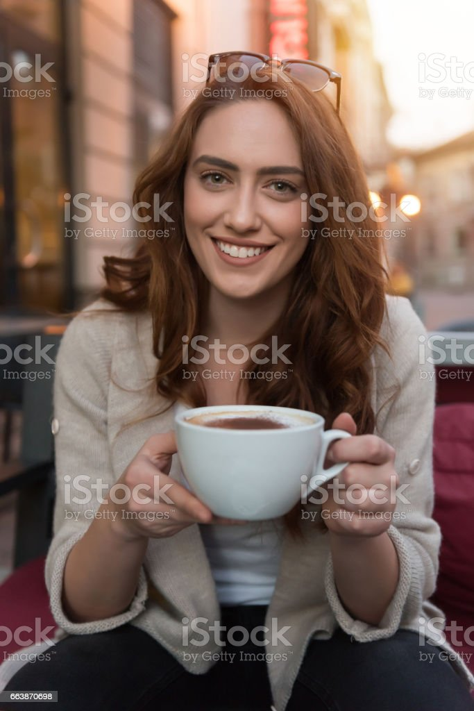 Charming girl drinking cappuccino stock photo