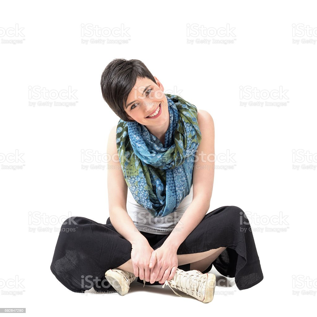 Charming girl sitting cross-legged smiling at camera with slanted head stock photo
