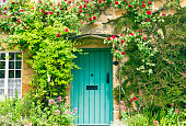 Charming House with green doors and red roses