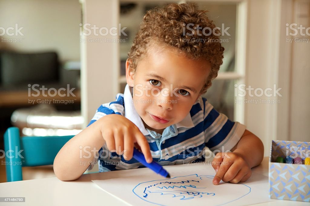 Charming Little Boy Busy Coloring at His Desk stock photo