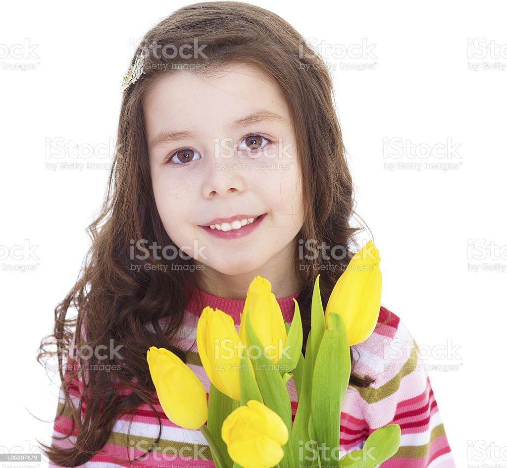 Jolie petite fille avec des tulipes jaunes. photo libre de droits