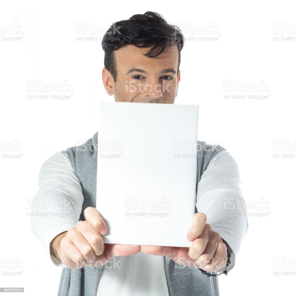 Charming man holds a blank and rectangular paper. Handsome brazilian wearing gray and white clothes, neutral. stock photo