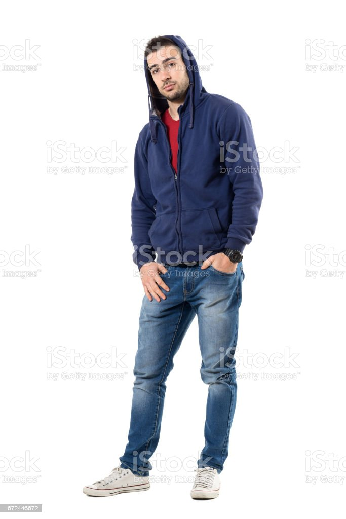 Charming man in blue hooded sweatshirt with hands in pockets looking at camera. stock photo