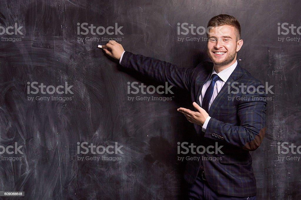 Charming man writes with chalk stock photo