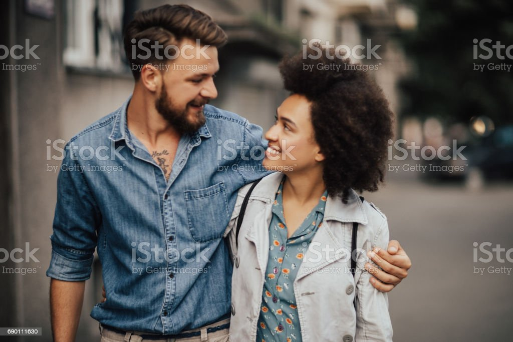 Charming multi-ethnic couple in loving embrace stock photo