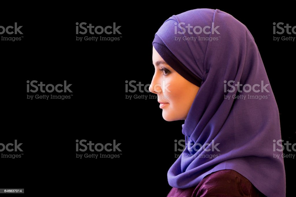 charming Muslim woman in a scarf on her head in profile stock photo