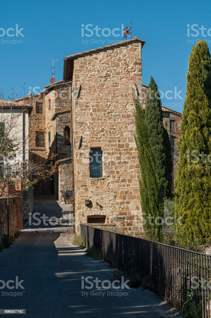 SAN QUIRICO D'ORCIA, ITALY - OCTOBER 30, 2016 - Charming narrow street in the town of San Quirico d'Orcia, province of Siena, Val d'Orcia, Tuscany, Italy stock photo