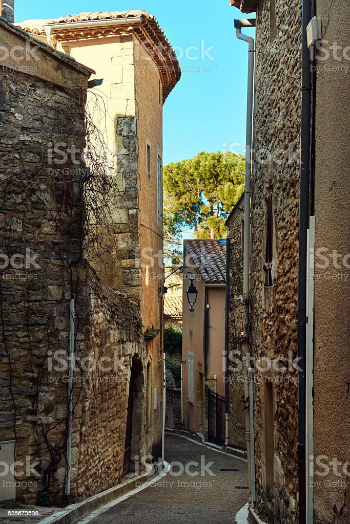 Charming narrow street of Venasque. France stock photo