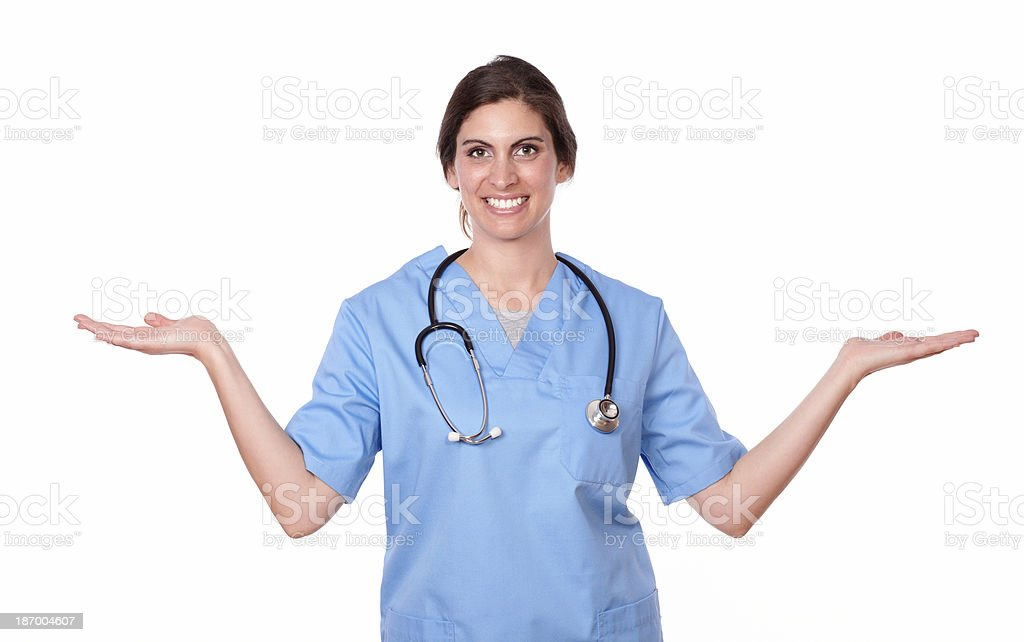 Charming nurse smiling holding her palms out royalty-free stock photo
