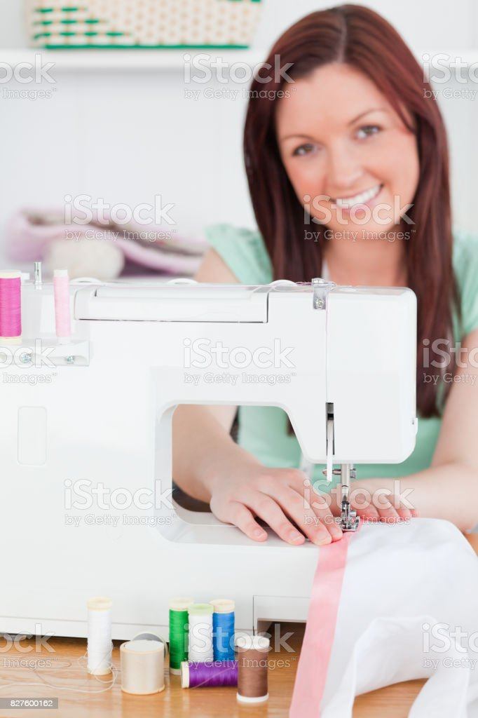 Charming redhaired woman using a sewing machine stock photo