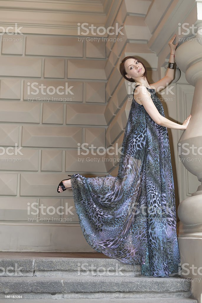 Charming sensual young woman in gauzy lengthy dress on stairs royalty-free stock photo