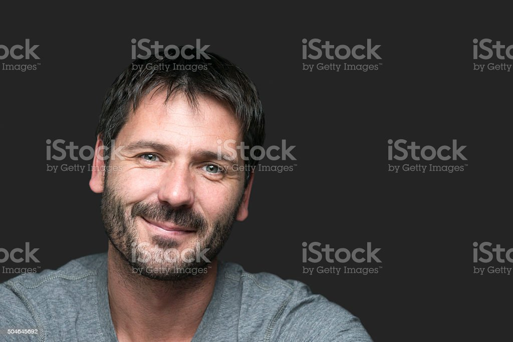 charming smiling man portrait isolated on gray stock photo