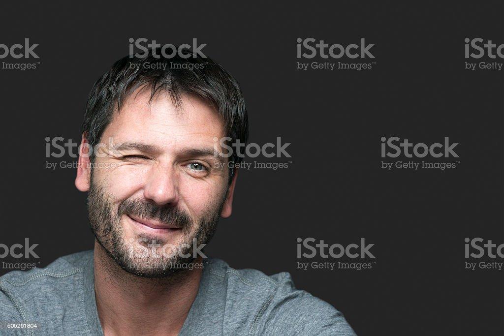 charming smiling man winking at camera stock photo