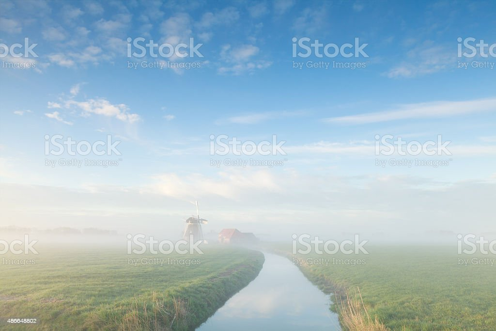 charming windmill by river in misty morning stock photo