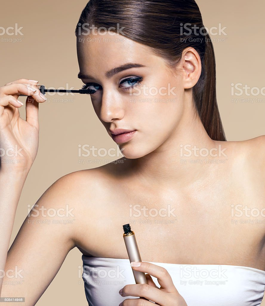Charming woman applying mascara stock photo