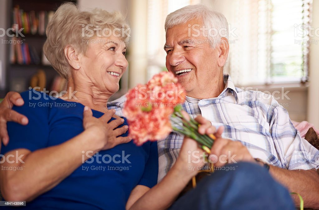 Charming woman is given a bunch of flowers stock photo