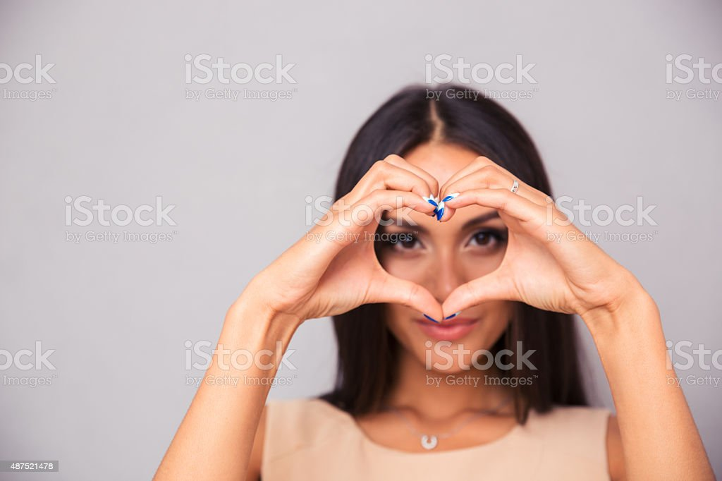 Charming woman making heart with fingers stock photo