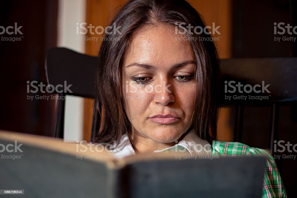 charming woman sitting reading book with serious expression stock photo