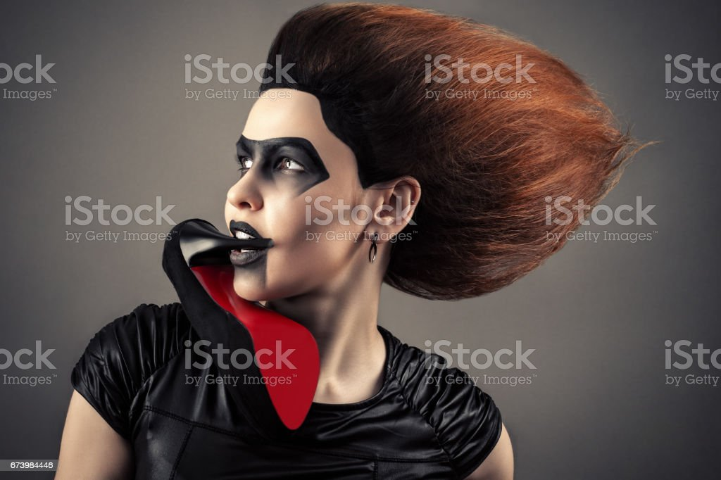 charming woman with a dark makeup and lush hairstyle with heel in mouth stock photo