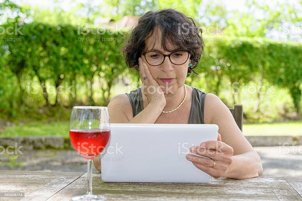 charming  woman with a tablet in her garden stock photo